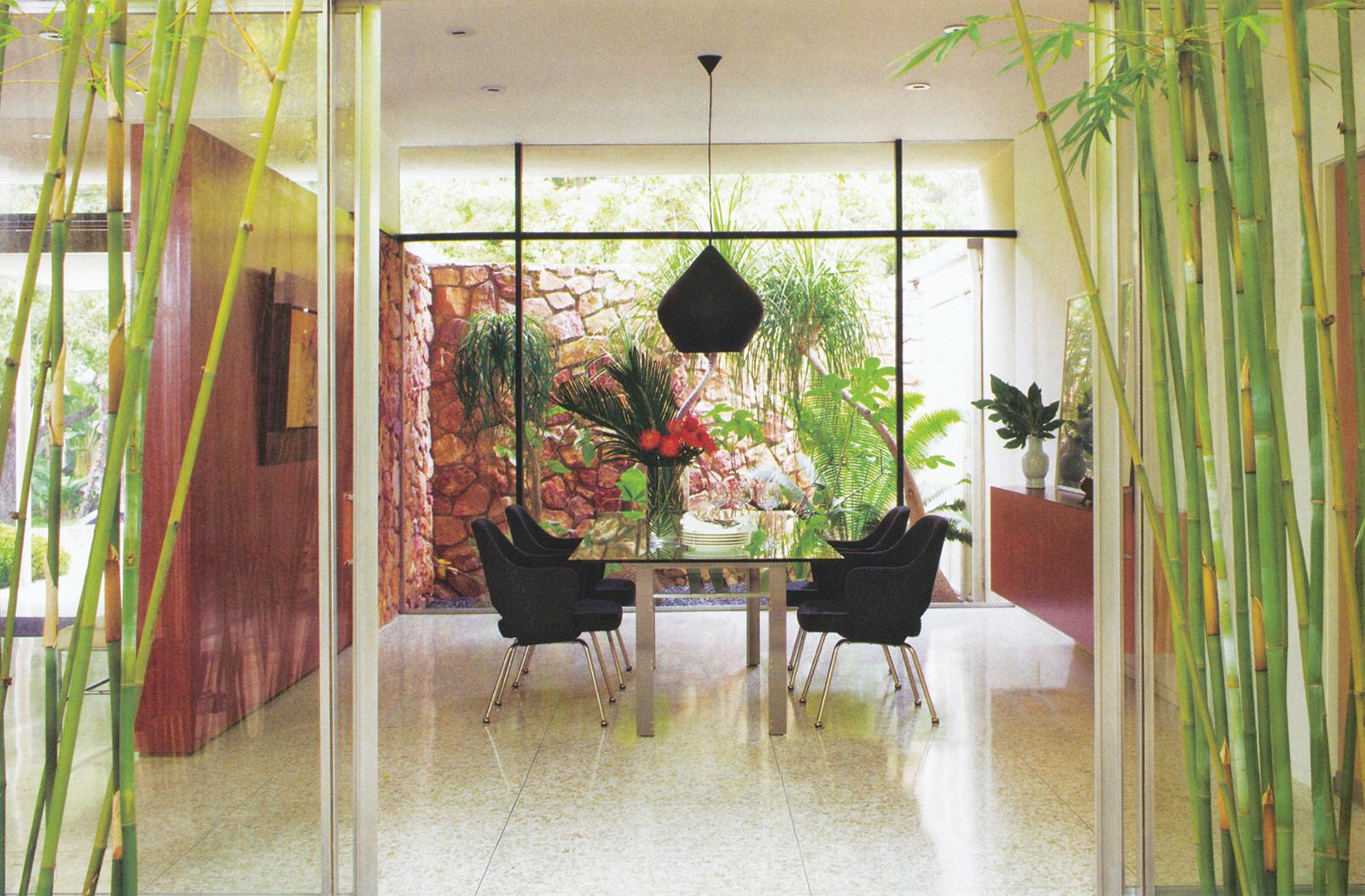 اتاق غذاخوری و سِت غذاخوری با صندلیهایی که طراحیشده توسط ارو سارینن برای شرکت نول هستند و یک چراغ سقفی سیاهرنگِ مدلِ بیت (Beat) طراحیشده توسط تام دیکسون در بالای این میز آویخته است.