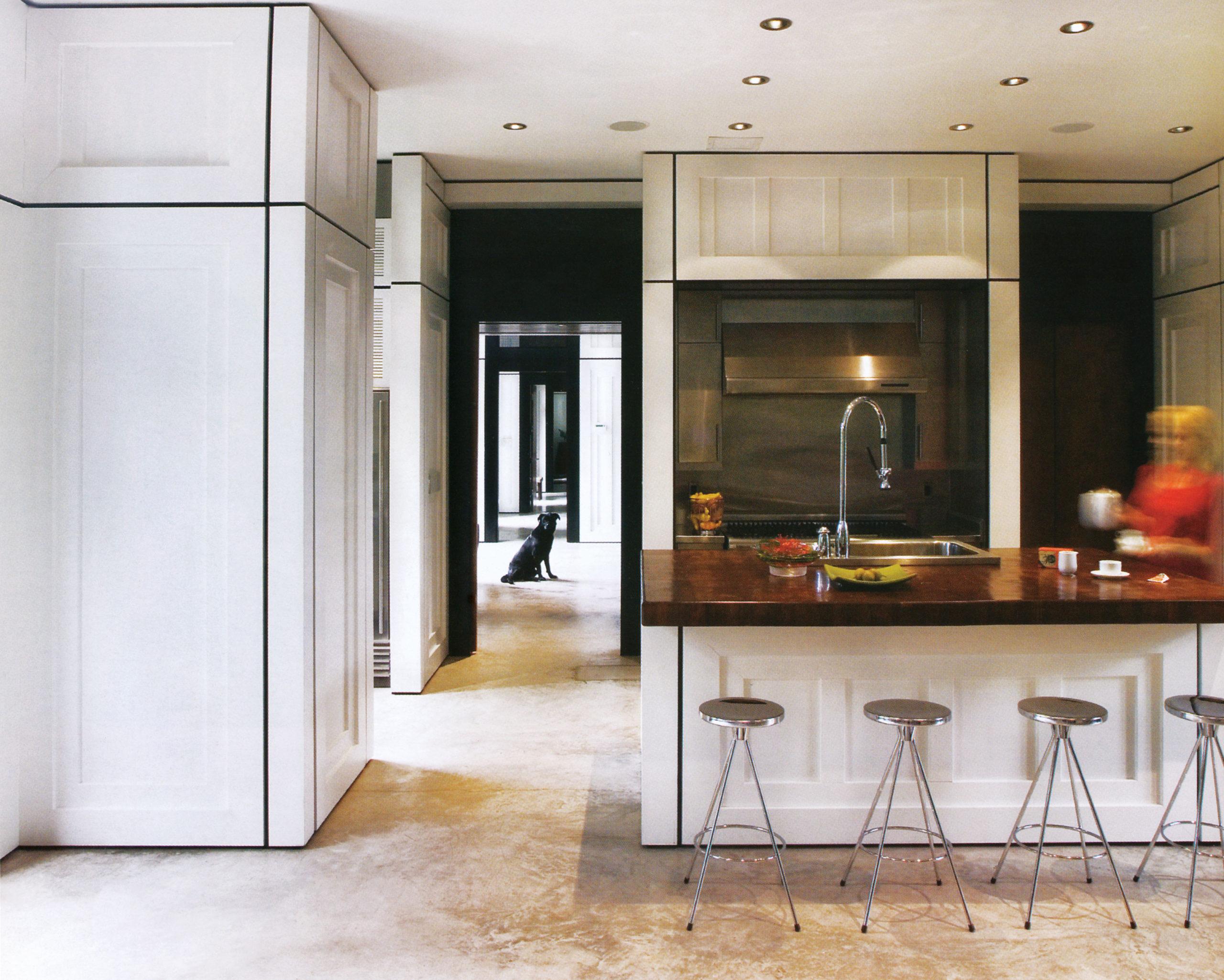 تختهای از جنس چوب کاج که بازماندهی مصالح خانهای است که پیشتر در این محل بود، در خانهی نوساز حکم کانتر آشپزخانه را پیدا کرده است. سینک و شیر آلات روی آن، از استیل ضدزنگ و کروم هستند و کابینتها، یکدست به رنگ سفید انتخاب شدند. در این آشپزخانه از گاز روکار استفاده شده است.